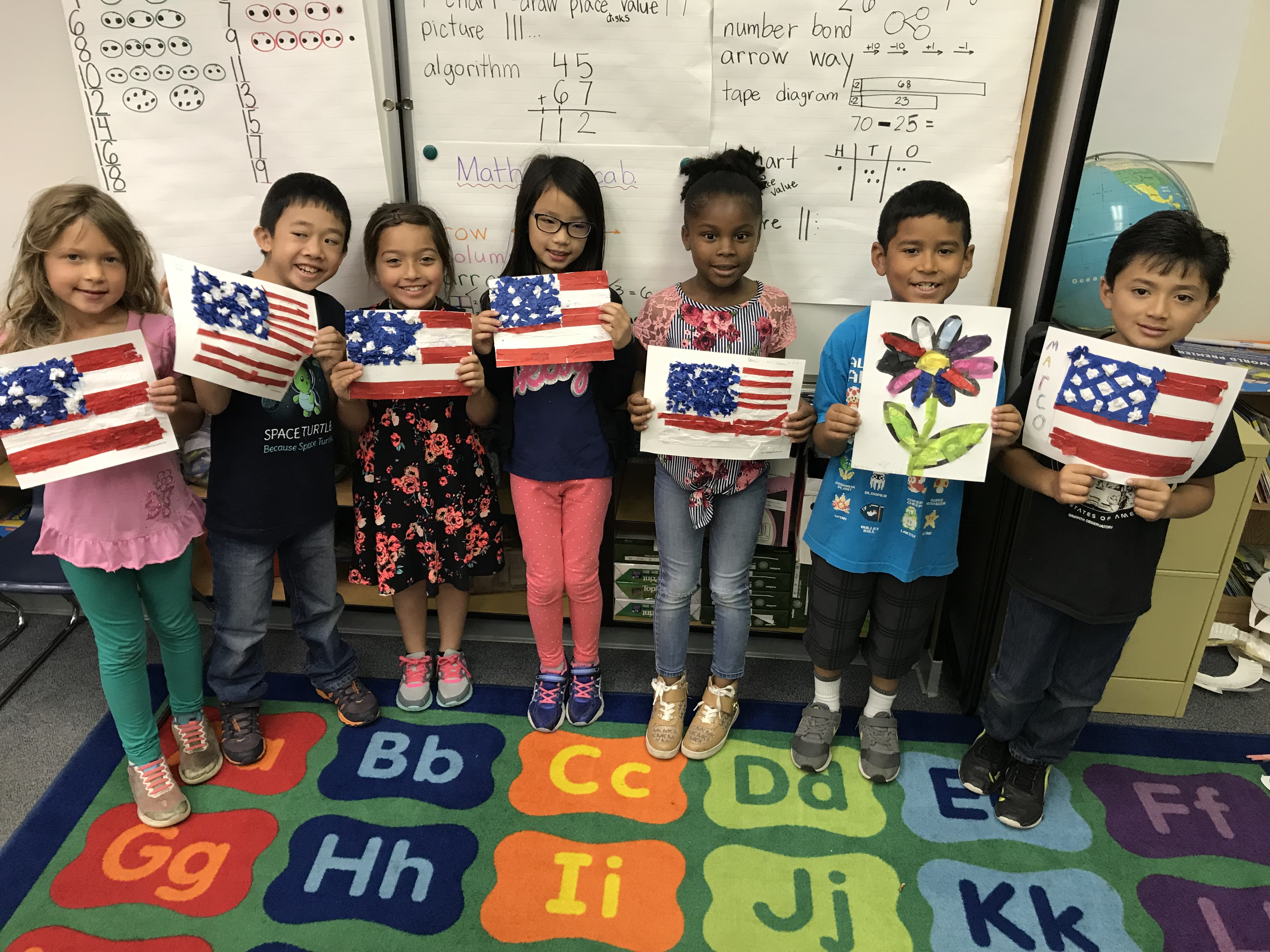 Children holding their art work of the american flag